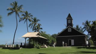 People arrive at a tropical church as the bell rings.