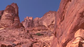 People climb up a steep canyon into the dry mountains of Wadi Rum, Jordan.