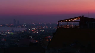 People eat dinner at a rooftop restaurant overlooking Istanbul, Turkey at dusk.