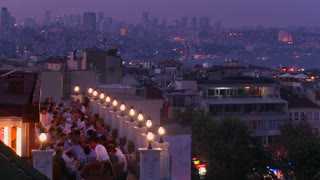 People eating dinner at a rooftop restaurant overlooking Istanbul, Turkey.