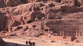 People ride donkeys and camels near the ancient amphitheater in the ancient Nabatean ruins of Petra, Jordan.