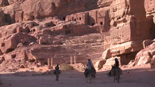 People ride donkeys near the ancient amphitheater in the ancient Nabatean ruins of Petra, Jordan.