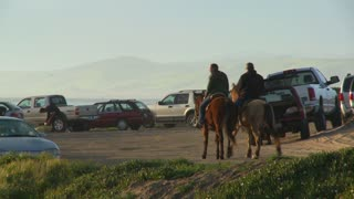 People ride horses along a beachside parking lot in California.