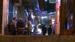 People walk in the Arab Quarter of the old city of Jerusalem at night.