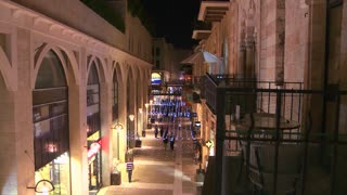 People walk through a modern shopping center in front of the old city walls of Jerusalem, Israel by night.