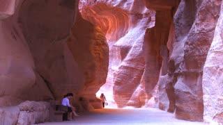 People walk through the narrow canyons leading up to Petra, Jordan.
