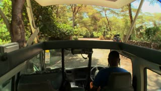 POV shot driving in an open topped safari vehicle through Africa.