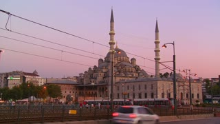 Rapid transit trams and traffic at dusk in front of a mosque in Istanbul, Turkey.