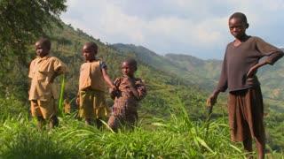 Rwanda children stand in farm fields.