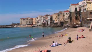Small ocean waves break near houses as families relax onshore in Cefalu, Italy.