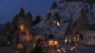 Strange dwellings built into a hillside at dusk or night in Cappadocia, Turkey.