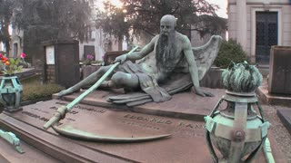 The grim reaper sits on a tomb in a graveyard with his scythe.
