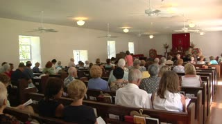 The interior of a small town church with many worshippers.
