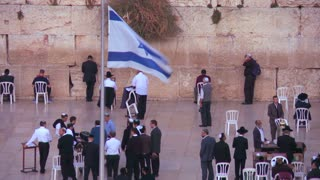 The Israeli flag waves in front of Jewish pilgrims praying at the Wailing Wall in Jerusalem, Israel.