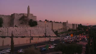 The old city walls of Jerusalem, Israel glow in dusk light.