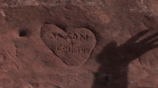 The shadow of a hand moves over a graffiti heart carved into sandstone.