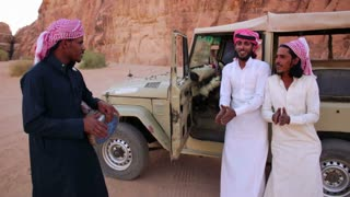 Three Bedouin men sing songs near their jeep in the Saudi desert of Wadi Rum, Jordan.