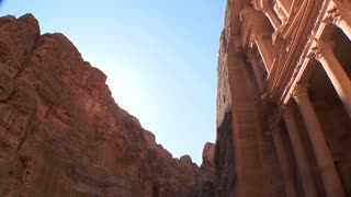 Tilt down to the facade of the Treasury building in the ancient Nabatean ruins of Petra, Jordan.