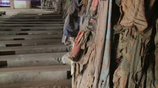 Tilt up reveals a Rwandan church following the genocide there with clothes of victims hung on walls.