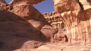 Tilt up to an amazing arch formation in the Sadi desert in Wadi Rum, Jordan with a Bedouin man walking through.