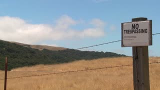Time lapse of clouds drifting past a no trespassing sign.