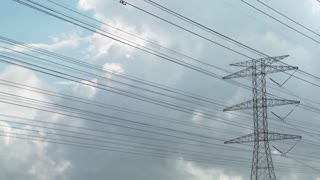 Time lapse of clouds moving behind high tension wires and power lines.