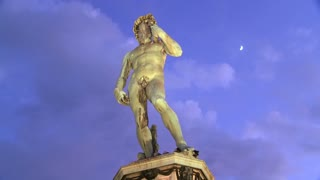 Time lapse of State of David at dusk in Florence, Italy with moon in background.