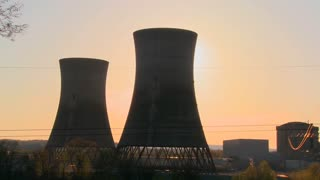 Time lapse shot of the sun setting behind a nuclear power plant.