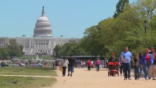 Tourists enjoy the summer weather in Washington DC with the Capitol Dome in the background.
