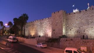 Traffic moves in front of the old city walls of Jerusalem, Israel by night.