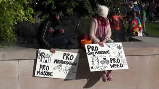 Two girls hold signs announcing they are in favor of masturbation, marijuana, mosques and gay marriage.