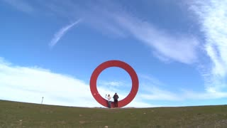 Two people sit on a sculpture of the letter o against an open sky.