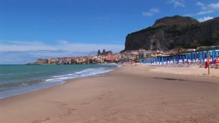 Umbrellas rest on a beach near houses and waves breaking in Cefalu, Italy.