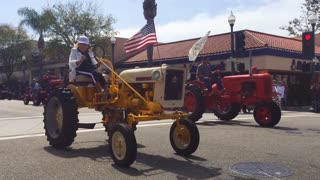 A senior lady farmer drives her tractor down a city street during a 4th of July parade in a small town.