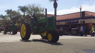 Farmers drive their tractors down a city street during a 4th of July parade in a small town.