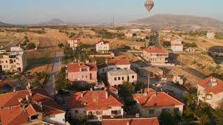 Hot air balloons fly over a neighborhood near Cappadocia, Turkey.