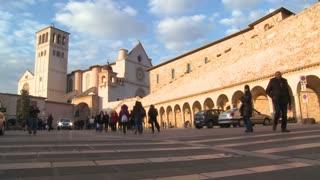 Visitors walk towards the main church at Assisi, Italy.