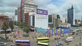 Wide shot of downtown Nairobi Kenya with traffic and pedestrians.