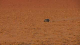 Zoom back to reveal a Bedouin truck driving fast across the vast desert sands of Wadi Rum, Jordan.