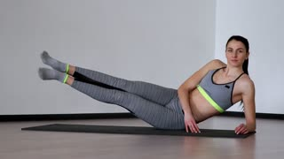 A beautiful brubnette in a gray sports suit makes a side bar and knocks with heels with straight legs. Pilates and static exercises
