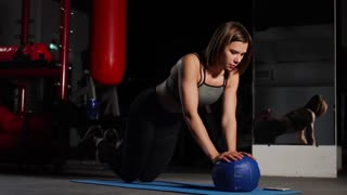 A brunette athletic builds push-ups on a mache in the gym putting a stopwatch on the mobile phone. Boxing training, Combat sports.