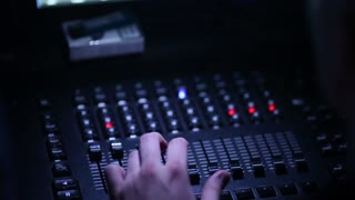 A close-up of a man's hand controls the sound equipment at a concert of a famous band. The sound panel