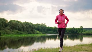 A girl in a pink jacket and black pants runs near the river in headphones preparing for the marathon