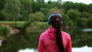 A girl in a pink jacket and blue headphones stands with her back and looks at the river early in the morning after a run
