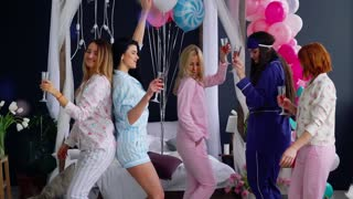 A group of dancing girls at a pajama party with glasses of champagne laugh and smile.