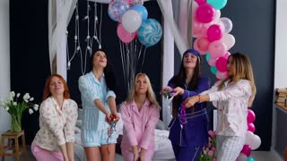 A group of girls laughing and smiling in pajamas launching confetti in slow motion 120 frames per second. Throw in the air shiny candy at the party. Bachelorette