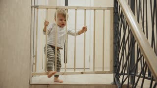 A little boy is sitting at home in front of the stairs behind the bars which will not allow it in another part of the house. Safety for the child