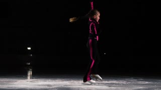 A little girl skater in a black sports suit and white skates performs a spinning stand in the arena of the ice stadium. On the average for figure skating
