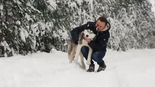 A man hugs his Siberian husky in the forest. In the background trees in the snow. Pride and happiness in the eyes. Walk with the dog