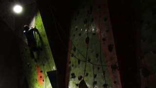 A man on a safety rope climbs the rock up. Slow motion